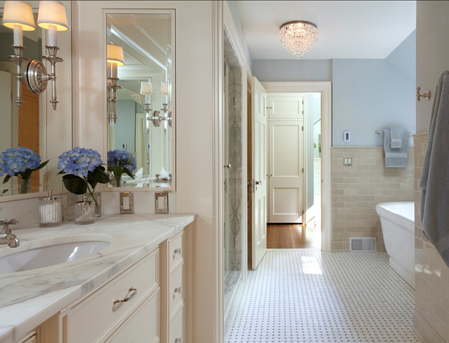 Bathroom Ideas. Bathroom with cream white cabinets and blue paint color on the walls. This bathroom feels classic with its basketweave marble floors and cream white cabinets. #Bathroom #BathroomIdeas #BathroomDesign Designed by Yunker Associates Architecture.