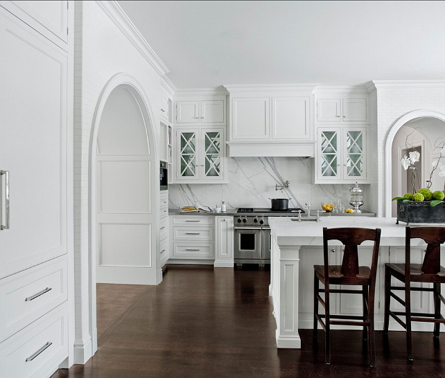Custom Kitchen Ideas. Custom built arch ways, glass upper cabinets with 'X' mullions, calacatta marble used on both back splash and built up counter top,stainless steel appliances, and integrated refrigerator and freezer. #Kitchen #CustomKitchen #KitchenIdeas