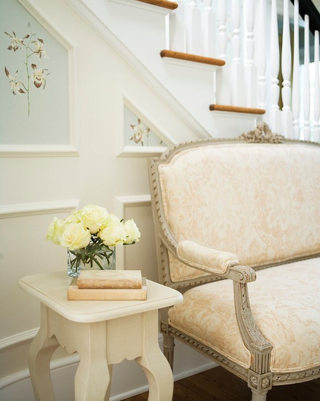 Entryway. Classic French Entryway. Elegant entryway with French gray settee upholstered in a blush pink damask fabric with an ivory cabriole leg side table to the left topped with ivory roses framed by wainscoting paneled staircase wall with handpainted floral panels.  #Entryway #FrenchInteriors