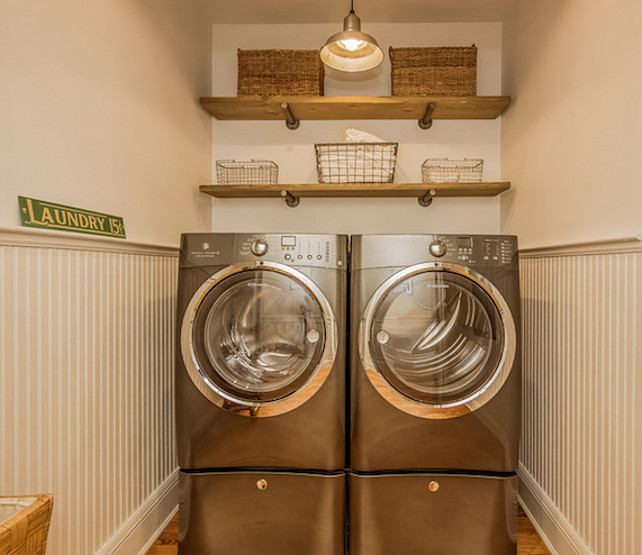 Laundry Room. Gray laundry room boasts light gray on top half of walls and gray beadboard on bottom half of walls framing reclaimed wood shelves filled with woven baskets and wire baskets. #LaundryRoom