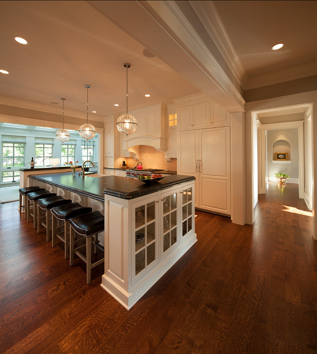 "Kitchen Design. The floors are 5"" Rift & Quarter Sawn White Oak, Select Grade, with a custom-blended stain. Kitchen Pendants are ""Janus globe pendant from Cyan Design"". Cabinets are painted in Benjamin Moore White Dove OC17. #KitchenDesign #Kitchen #KitchenIdeas #WhiteKicthen"