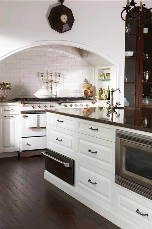 Kitchen Range Ideas. This traditional kitchen boasts intricate details along with thoughtful design. A prep sink adjacent to the white La Cornue range top, a large blower disguised under a cooking niche, and integrated appliance contributes to the effortlessness of the overall space. Traditional Kitchen Range. #Kitchen #Range