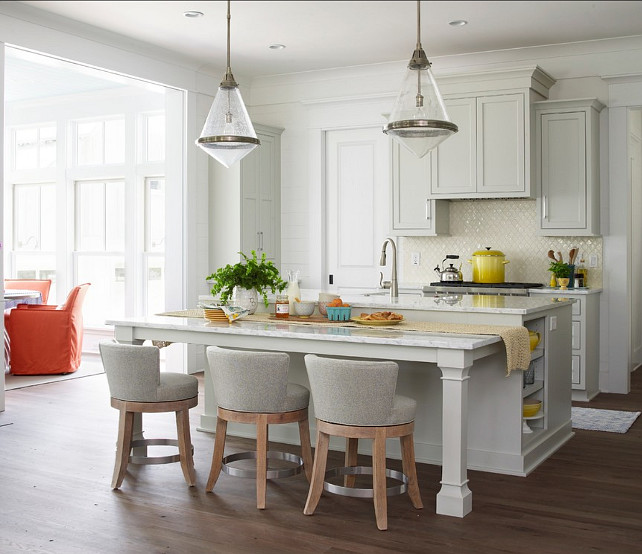 "Kitchen. Pale Gray Kitchen. Transitional Kitchen with pale gray cabinets. The kitchen feature pale gray cabinets with clean lines and transitional lighting.  Pendants are the ""Thomas O'Brien - Gale Pendant"" by Circa Lighting.  The swiveling barstools are from Lee Industries.  The MotionSense faucet is by Moen. #Kitchen #KitchenIdeas #GrayKitchen #KitchenCabinets #TransitionalKitchen #KitchenDesign"