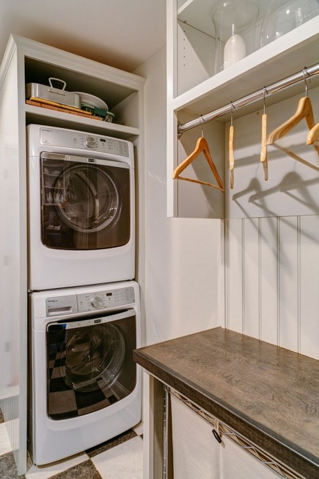 Laundry Room. Laundry Room Design Ideas. Cottage laundry room boasts stacked washer and dryer encased in beadboard cabinetry across from shelving over clothes rail with beadboard backsplash above clothes bin sorters tucked under wood countertop. #LaundryRoom #LaundryRoomDesign #LaundryRoomPhotos #SmallLaundryRoom Designed by Sandy Muraca Design.