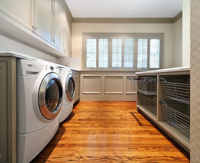 Laundry Room Ideas. Huge laundry room with white washer & dryer, gray cabinets, gray painted wainscoting, gray laundry island and wire bins. #laundryRoom #LaundryRoomIdeas