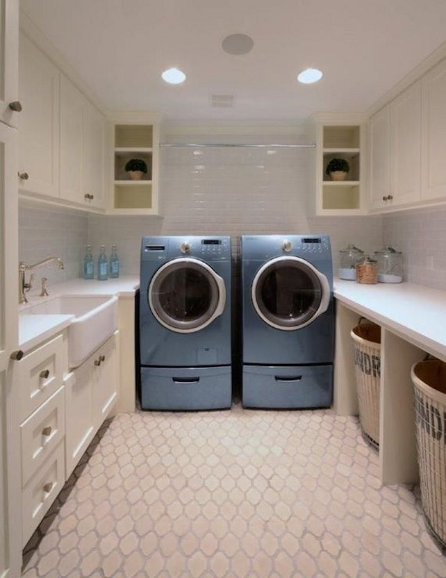 .Laundry Room Design. U-shaped laundry room has ivory cabinets with white quartz countertops and subway tiled backsplash atop an arabesque tile floor. Over the blue front-load washer and dryer is a tension rod.