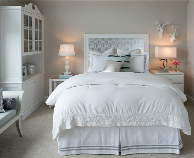 Neutral Bedroom. Beautiful neutral bedroom with greige wall paint color. Neutral Bedroom. Beautiful neutral bedroom with greige wall paint color. Designed by Studio M Interiors. #Bedroom #GrayBedroom #GreyBedroom #GreigeBedroom #Greige This gray and white bedroom features a custom silver patterned headboard with white frame. The bed is flanked by a white nailhead side table with a white stacked sphere lamp to the left and a 2-drawer nightstand with Chanel lamp on the right below a pair of faux taxidermy deer mounts. The bedroom is finished with a white glass topped hutch to the left, beside an ivory and gray bench, with figurative fashion art on the opposite wall. #Bedroom #GrayBedroom #GreyBedroom #GreigeBedroom #Greige