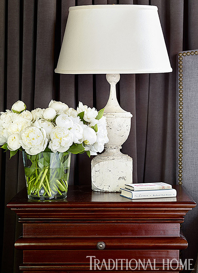 Nightstand Decor. Nightstand Decor Ideas. The nightstand, in Hand Rubbed Brown, blends with the dark hues of the master bedroom. White accents, like the lamp from Bungalow Classic and a vase of roses provide contrast. #Nightstand #NightstandDecor #Bedroom
