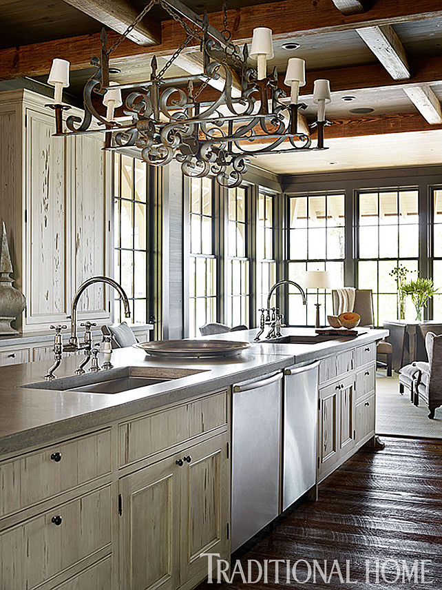 Rustic Kitchen Ideas. Beautiful Kitchen with rustic elements. Inspiring kitchen island with two large Kohler sinks fitted with Waterworks bridge-style faucets. Countertop is concrete. The iron chandelier is from Foxglove Antiques. #Kitchen #RusticKitchen #KitchenIsland