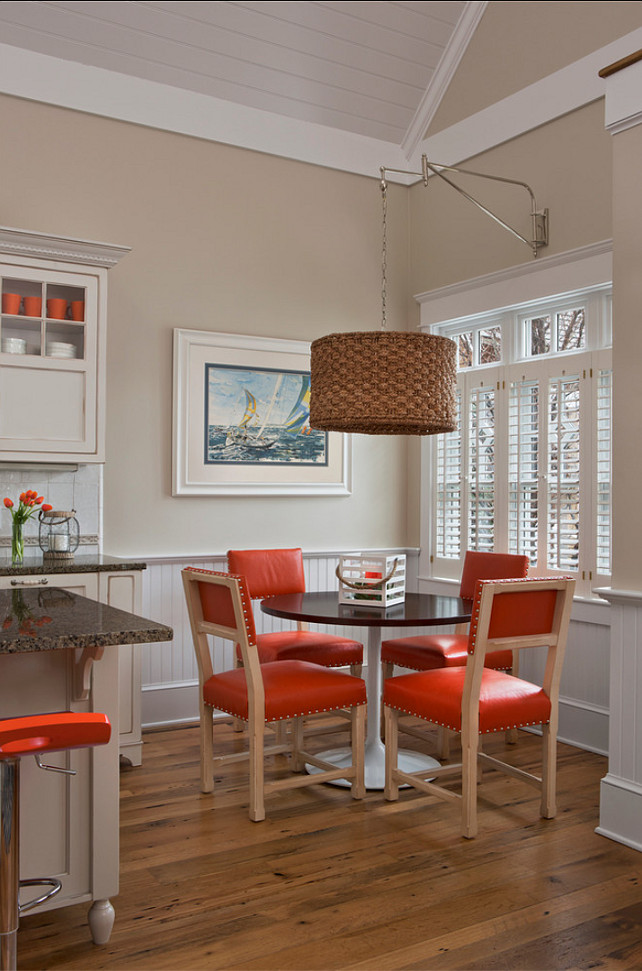 Transitional Interiors. Transitional eacting nook with hints of orange decor. #TransitionalInteriors #OrangeInteriors Designed by Cottage Company Interiors.