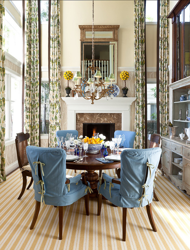 Dining Room. A dedicated dining room – with 20-foot-high ceilings – is situated on the site of the former traditional living room and features understated touches such as blue slip covered chairs and a yellow and white striped carpet.